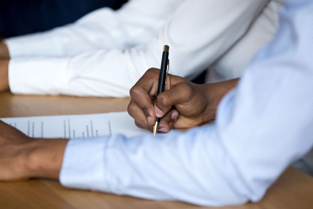 Man's hand holding a pen, signing a form