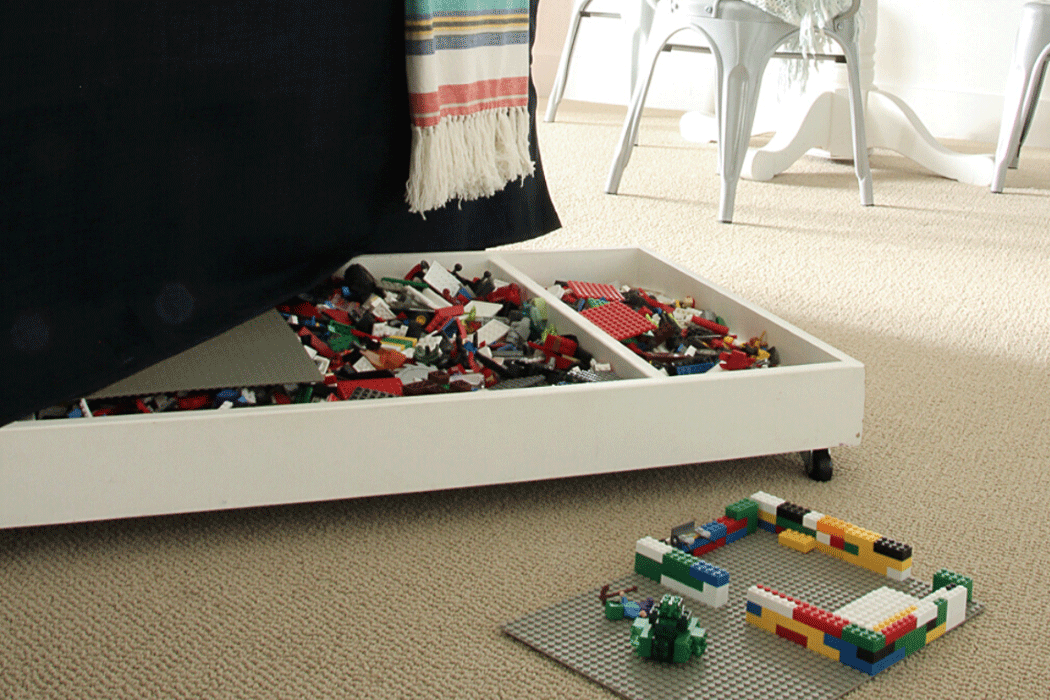 Low, flat toy storage bin filled with small toys, peeking from beneath a couch