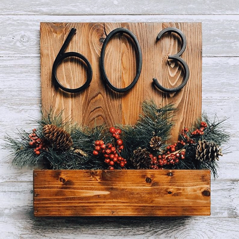 House number plaque with attached planter box filled with pine boughs and cones