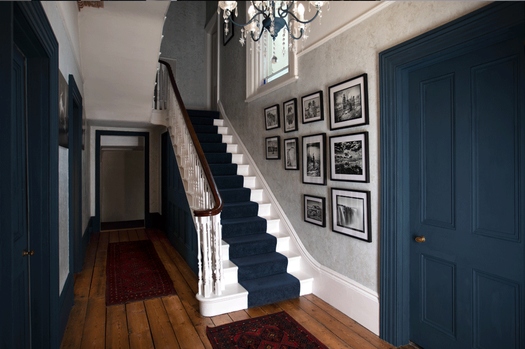 Narrow staircase in the hall of a Victorian-style home.
