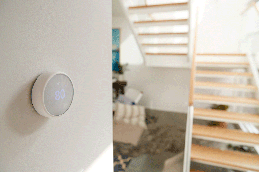 Smart thermostat attached to a wall with nearby stair case