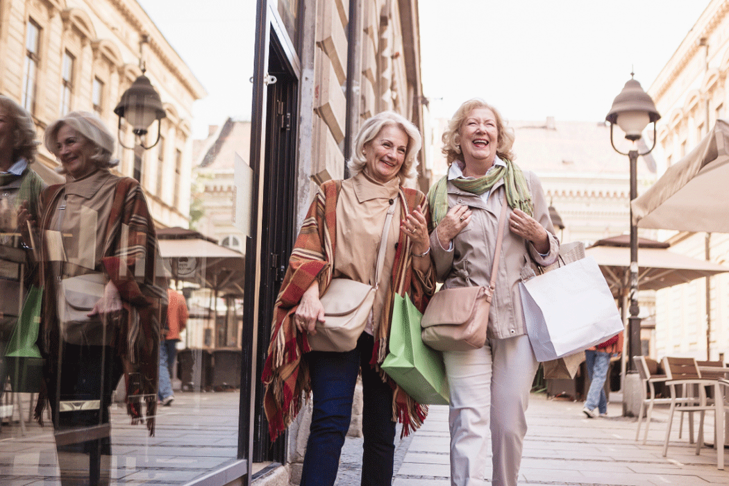 Two retired women with shopping bags laughing in the street