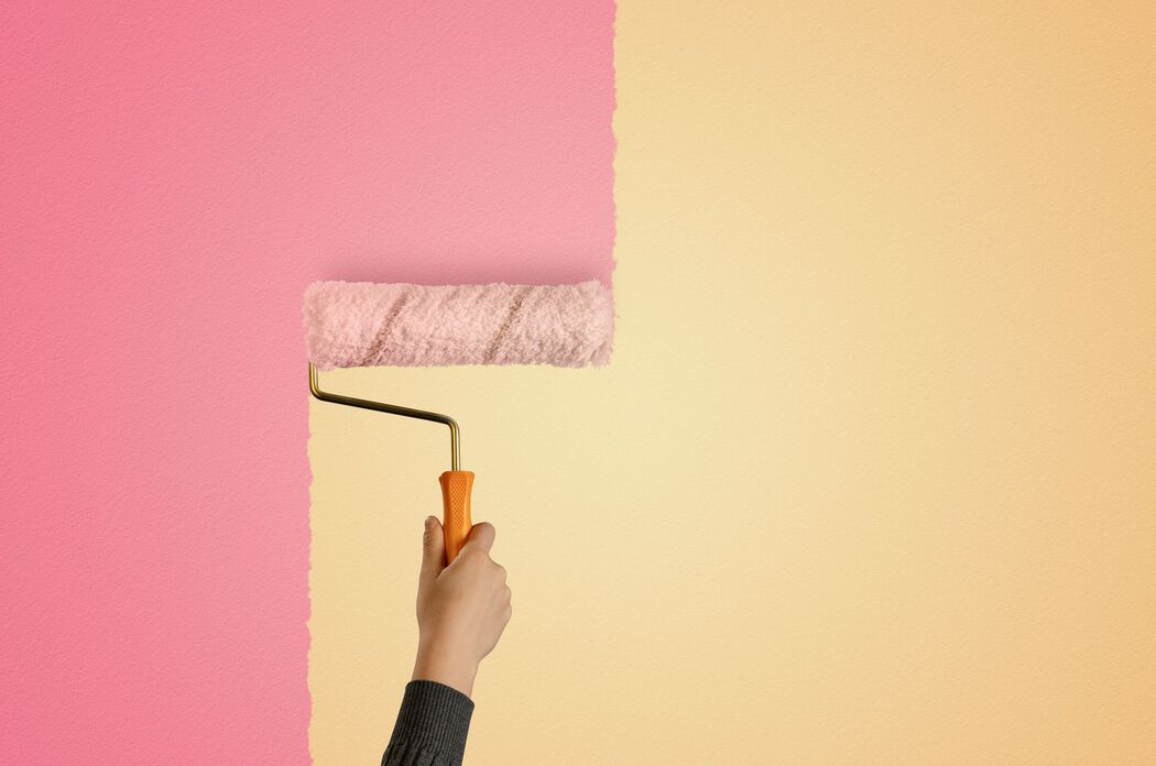 Close up of paint roller changing room from yellow to pink