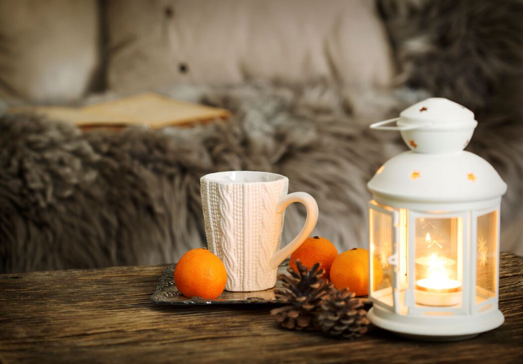 Tabletop with mug, clementines, pine cones, candle