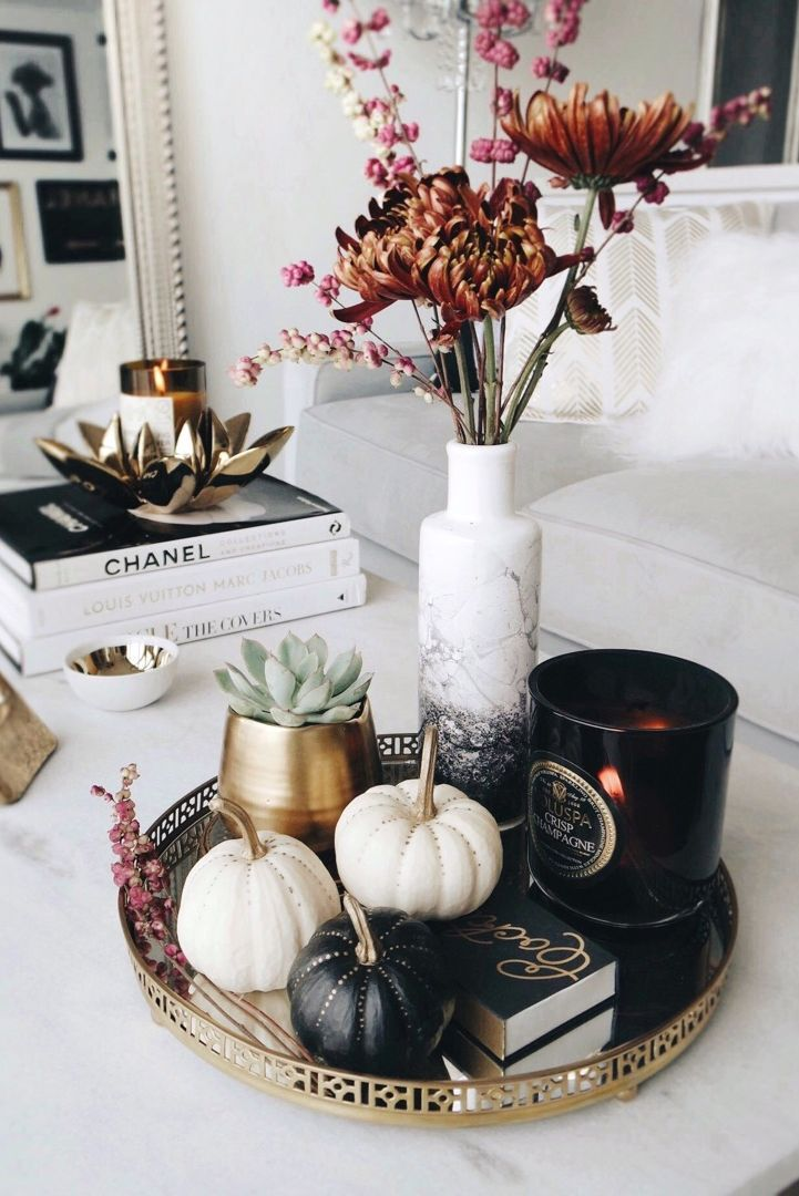 Black, gold and white-painted miniature pumpkins with flower vase and candle on a gold tray