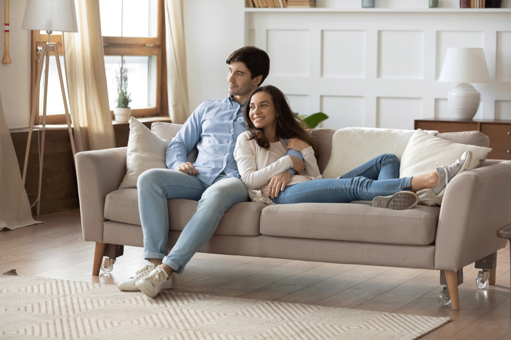 Couple sitting on a couch, contentedly looking around at their new home
