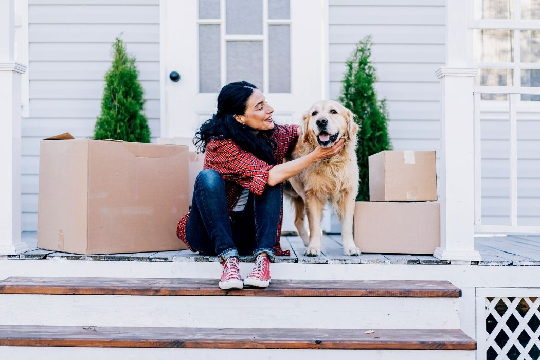 Woman with a dog on the front porch surrounded by moving boxes