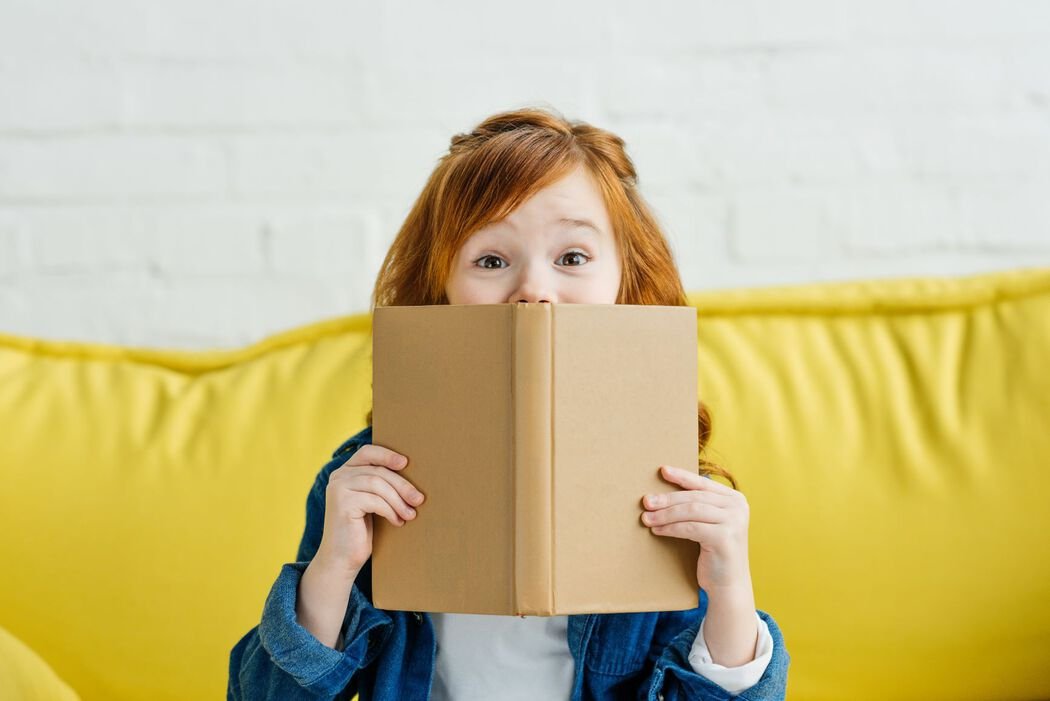 Young girl with a book half covering her face on yellow couch