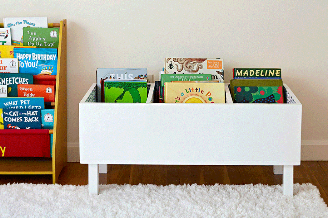 Short book bin with books peeking out of the top in a child's room