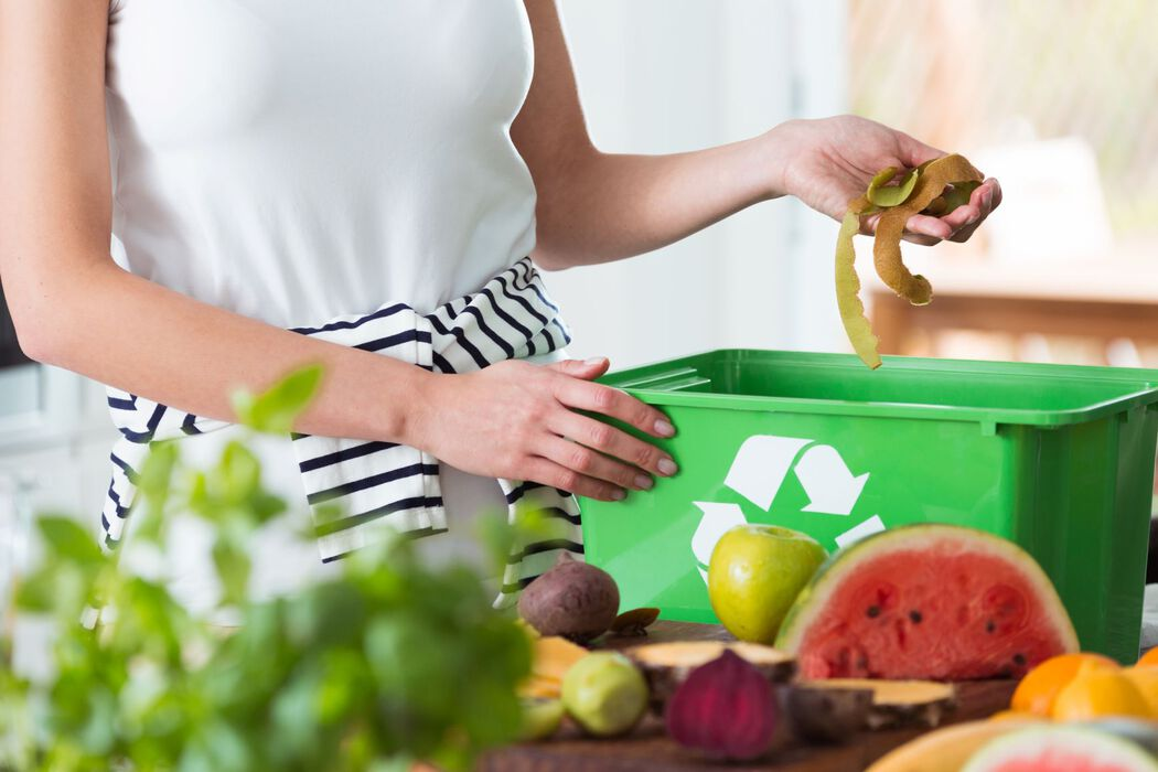 Woman composting in kitchen