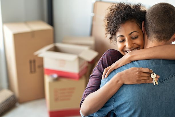 Couple in new house hugging with keys