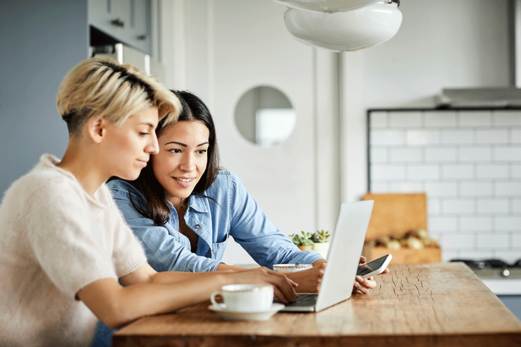 A couple looking at a laptop at a kitchen table