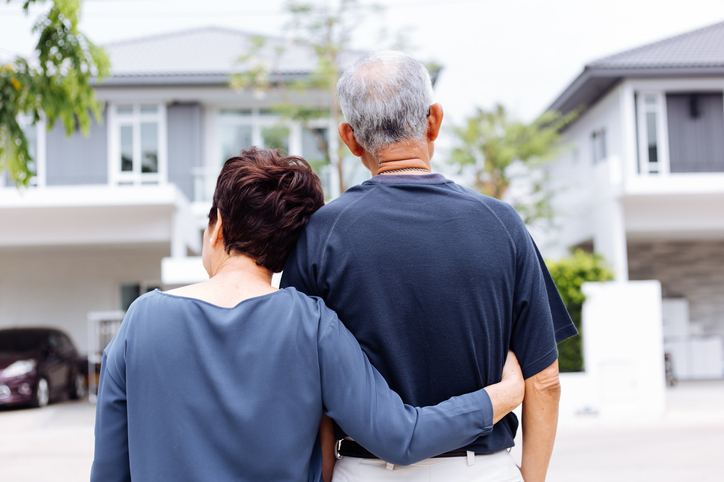 Couple looking sadly at old home