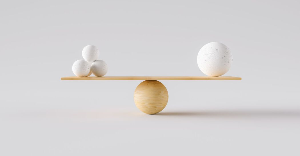 Conceptual image balance featuring balls stacked at either end of a plank of wood