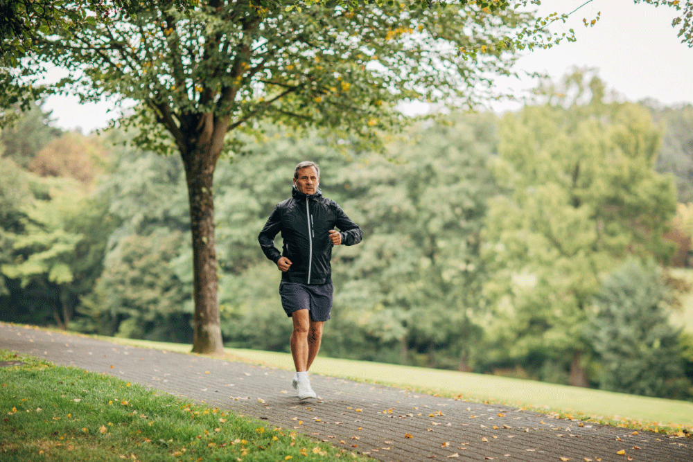 Grey-haired man jogging on a path overlooking a treed hill