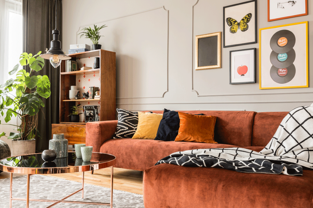 Warmly furnished living room with cinnamon-coloured velvet couch and yellow, black, and brass accent colours