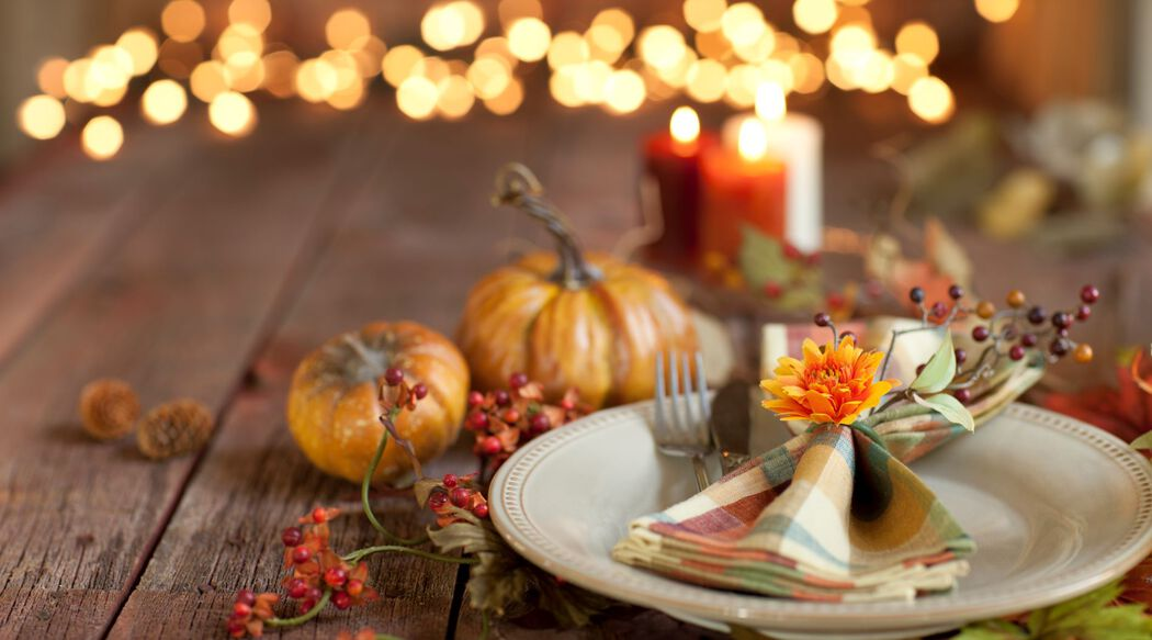 Fall dinner place setting with pumpkins and candles