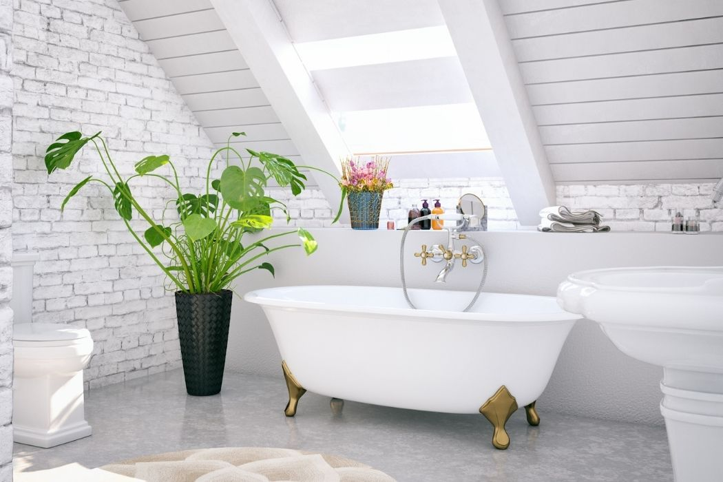 Attic bathroom featuring a skylight and all-white decor