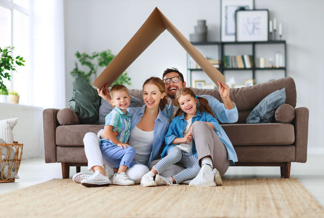 Family under cardboard piece mimicking a rooftop shape in a living room