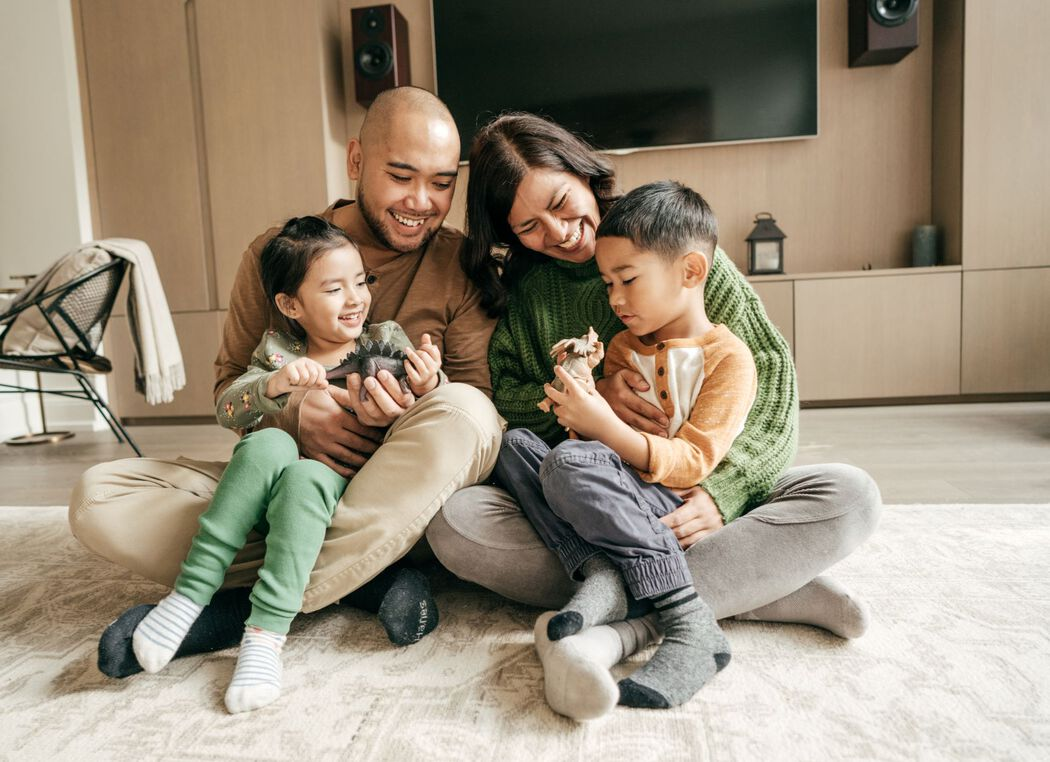 Happy family of four sitting on the floor