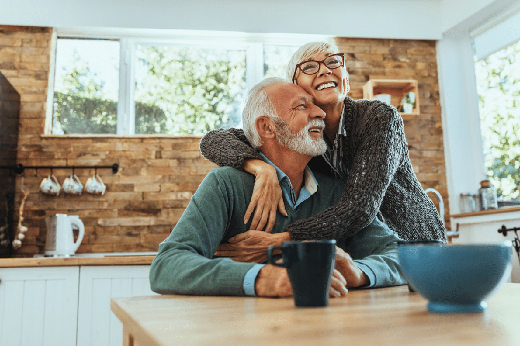 Retired couple smiling in a sun-filled kitchen