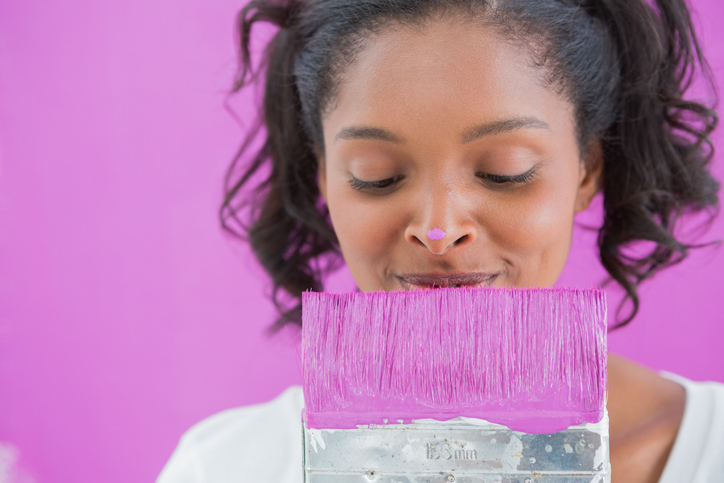 Woman looking at paintbrush for small home repairs