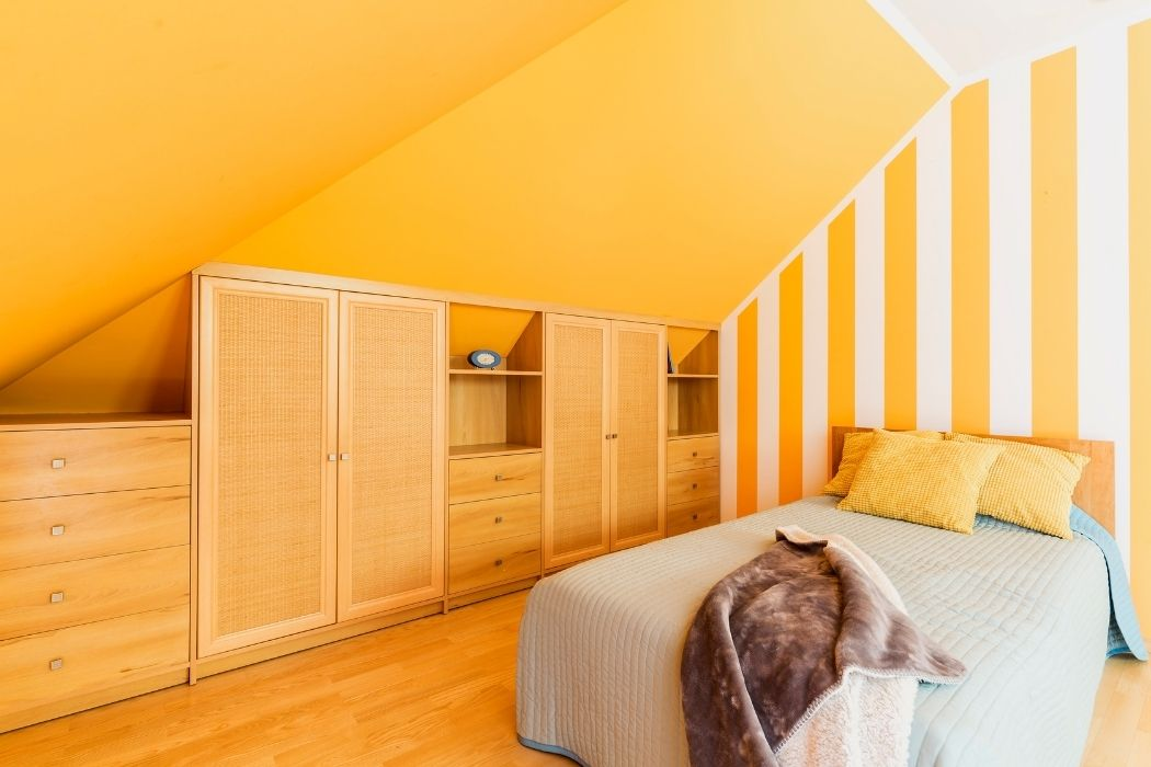 Bright orange attic bedroom with built-in drawers and cabinets