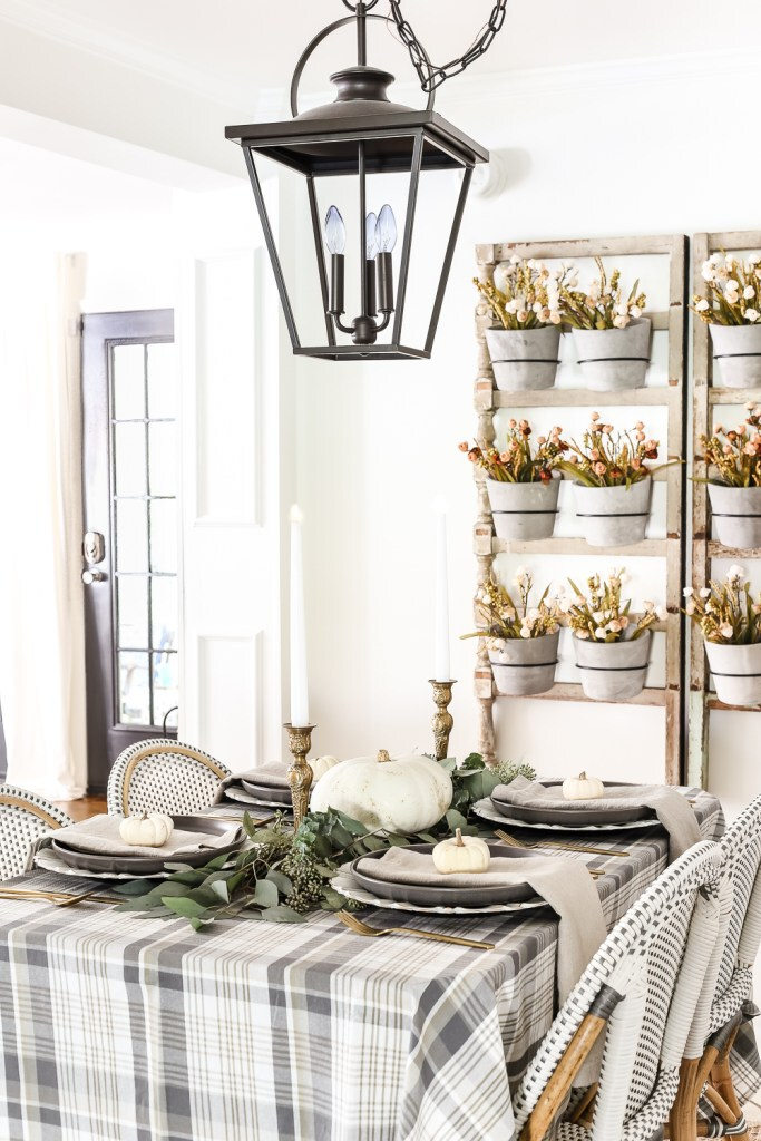Thanksgiving tablescape with white pumpkins, grey linens, and brass flatwear
